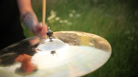 cymbals : man musician drummer hitting on wet drum cymbal, and the water splashing from cymbal in slow motion, on the street, in the day in sunny weather, around green grass, Close up