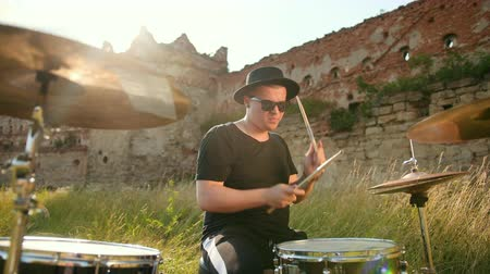 cymbales : man musician drummer dressed in black clothes, hat, with an earring in his ear, rhythmically playing the drum set and cymbals, throws and twists drumsticks, on street near old castle, on a Sunny day Vidéos Libres De Droits