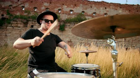 bassê : male musician drummer dressed in black clothes, hat, with an earring in his ear, emotionally playing the drum set and cymbals, on the street near the destroyed building, on a Sunny day Stock Footage