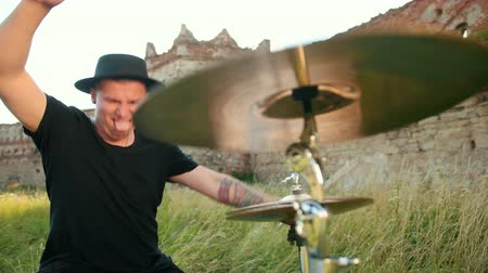 cymbals : man drummer, rock musician dressed in black clothes, hat, with an earring in his ear, emotionally playing the drum set and cymbals, on the street near the destroyed building, a day, slow motion Stock Footage