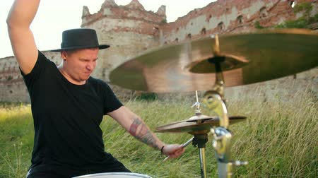 bassê : male musician drummer dressed in black clothes, hat, with an earring in his ear, emotionally playing the drum set and cymbals, twists drumsticks, on the street near the destroyed building, slow motion Stock Footage