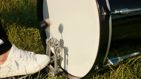 cymbals : man professional drummer, rock musician, rhythmically playing the drum set, in white sneakers presses the drum pedal, on the street, in the day, around the green grass, close-up, slow motion