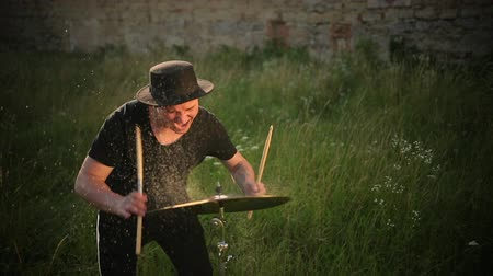 cymbals : man musician dressed in black clothes, hat, with an earring in his ear, drummer hitting on wet drum cymbal, and the water splashing from cymbal in slow motion on the street near ruined castle Stock Footage
