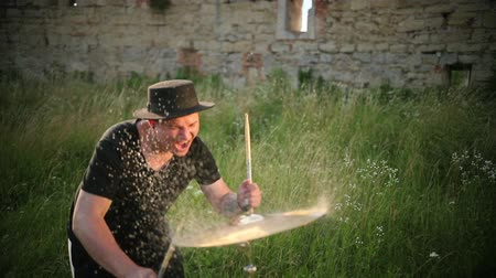 chapel : man musician dressed in black clothes, hat, with an earring in his ear, drummer hitting on wet drum cymbal, and the water splashing from cymbal in slow motion on the street, in the day