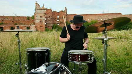 strik : man musician drummer dressed in black clothes, hat, with an earring in his ear, rhythmically playing the drum set and cymbals, throws and twists drumsticks, on street near old castle, on a Sunny day Stockvideo