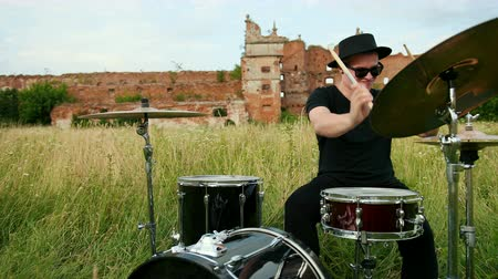 buben : male musician drummer dressed in black clothes, glasses and hat, energetically playing on the drum set, on the street, near the destroyed building on a Sunny day, around the tall green grass