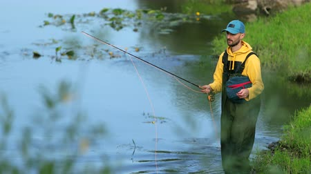 fly fishing : man fisherman in a yellow jacket and cap special clothes, throws a float, fishing on the river, standing in the water, green grass, beautiful nature, in the summer, in the day, slow motion