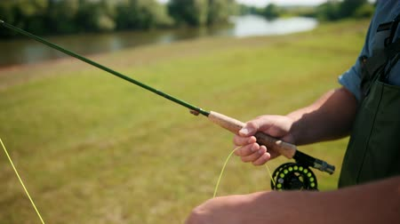 fly fishing : fisherman, fishing, holding a fishing rod, stringing bait, spinning reel, on the street, by the river, standing on the shore on the green grass, Sunny weather, blue sky, summer, close-up, slow motion