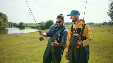 fly fishing : two men fisherman, with black hair and beard, green overalls, holding a fishing rod and a float, communicate with each other, smile, on the street, by the river on the grass, Sunny weather, close-up