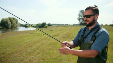 fly fishing : man fisherman, with black hair and beard, in a blue jacket, green overalls, holding a fishing rod and a float, turns the coil, on the street, by the river on the grass, summer, day, close-up