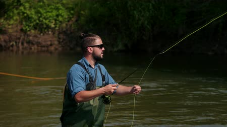 activities : fisherman with a beard and dark hair in special clothes, glasses, throws a float, a man fishing on the river, standing in the water, a small current, the nature is beautiful, summer, close-up