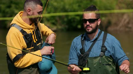 divergeren : two people fisherman brunettes with a beard in green overalls holding fishing rods in their hands, go fishing on the river, diverge in different directions, on a Sunny day, Close up, slow motion Stockvideo
