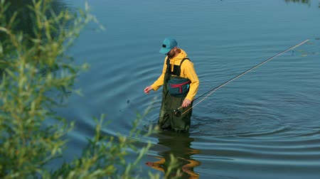 fly fishing : male fisherman in yellow jacket and blue cap special clothes, throws a float, fishing on the river, standing on the shore, on green grass, beautiful nature, in the summer day, Wide angle, slow motion