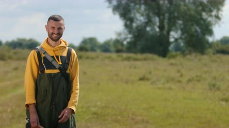 döküm : a young man, a beautiful slender, with short hair and beard, in a yellow jacket and green overalls, with a fishing rod in his hands, a fisherman posing in front of the camera, outdoors, on a Sunny day