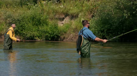 fly fishing : two men in special clothes holding fishing rods, fishing, people fishing on the river, standing in the water, a small current, the nature is beautiful, summer day, Wide angle, slow motion Stock Footage