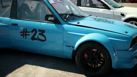 arrasto : LVIV, UKRAINE - JUN 01, 2019: blue car for street racing drift, with numbers on the doors, with reinforced body, wide wheels and large black discs and diode spotlight on the roof