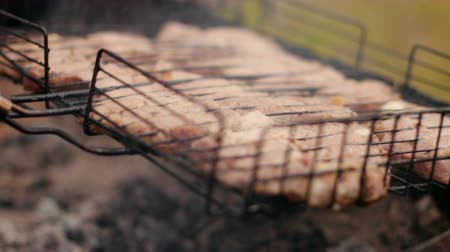ground meat : man prepares large pieces of meat on the grill, turning for roasting