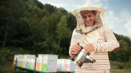 опылять : human beekeeper in special clothes, holding a smoker to calm the bees Стоковые видеозаписи