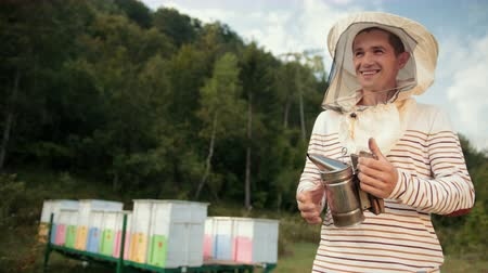 arı kovanı : human beekeeper in special clothes, holding a smoker to calm the bees Stok Video