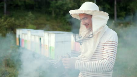 улей : man beekeeper in special clothes, holding a smoker to calm bees, a lot of smoke Стоковые видеозаписи