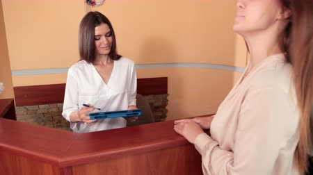 droogkast : nurse in medical gown provides advice to woman client at reception