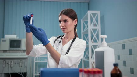 espécime : nurse doctor holding a test tube, carefully examines it