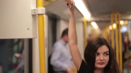 handrails : girl in black clothes riding subway and holding on to yellow handrails