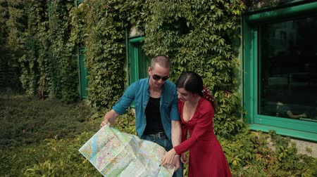 dönt : young couple in love, girl and man, holding map of city, decide where to go
