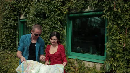 decidir : young couple in love, brunette girl in red dress and man in blue shirt and glasses, holding map of city, decide where to go, background house in green bushes, summer day, Sunny weather, slow motion Stock Footage