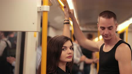 utas : transportation. two young people riding the subway, brunette girl with long hair and tall guy in black t-shirt holding on to the handrails, traffic, close-up, slow motion