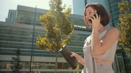 discar : business young woman, brunette, in light suit with small black bag, is large building with many Windows, business center, pull smarton and with smile talking, Sunny weather, a gentle breeze blowing Stock Footage