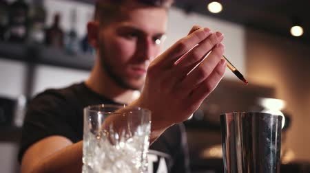 ginástico : bar counter. on which stands an engraved glass with ice for drink, young handsome bartender with beard drips ingredients from pipette into shaker, mixing cocktail, slow motion, close up Stock Footage