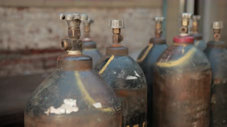 extinguishing : on street near old buildings, plant, are worth many gas cylinders, slow motion, close up