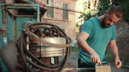 resmedilmeye değer : Young man with dark hair and beard, blue t-shirt is worth near old buildings, plant, clicks on button faulty, rusted mechanism, on which lie many rubber belts, sunny day Stok Video