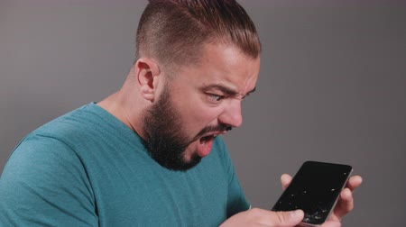 členění : Young man with dark hair and beard, blue t-shirt holding broken smartphone over gray isolated background with his mouth wide open he feels surprise and disappointment looking at broken screen of phone Dostupné videozáznamy