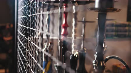 behind bars : hookah bar. many various hookahs are behind bars, process of making hookah for smoking. concept of smoking a hookah and having a good time, slow motion, close up