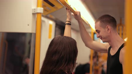 utas : transport. two young people riding the subway, brunette girl with long hair and tall guy in black t-shirt holding on to the handrails, traffic, close-up, slow motion Stock mozgókép