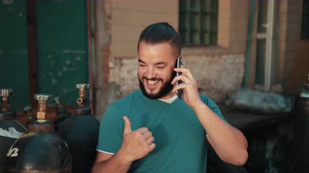 amoroso : Young man with dark hair and beard, blue t-shirt holding smartphone, standing near old building, factory, talking on phone, showing thumbs up sign OK, considers gas cylinders