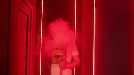 egyiptomi : hookah bar. young man with blond hair in a white t-shirt stands in red room and smokes hookah, produces a lot of thick smoke, slow motion, close up Stock mozgókép