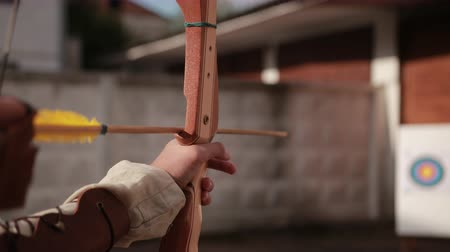 unlucky : archery. guy shoots from string, wooden arrows with yellow end of fly in white foam on which hangs target, on backdrop of wall, close-up, slow motion Stock Footage