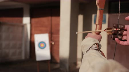 unlucky : archery. guy shoots from string, wooden arrows with color end of fly in white foam on which hangs target, on backdrop of wall, close-up, slow motion