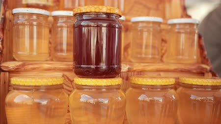 종류 : on wooden shelf there are many jars of honey, two kinds, closed with white and yellow lids, close-up, slow motion