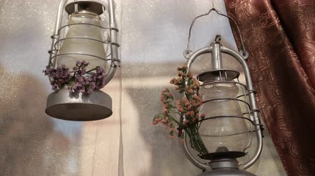 post room : two metal silver lamps hanging on shiny tulle near brown curtain, near lamps are small flowers of purple and orange flowers, close-up, slow motion Stock Footage