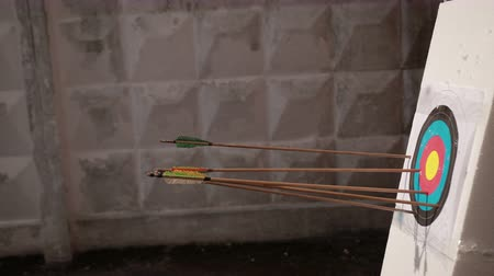 unlucky : archery. wooden arrows with colored end fly into white foam on which target hangs, in background wall, close-up, slow motion