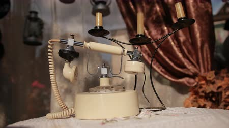 castiçal : on table with knitted tablecloth there is an old white telephone and candlestick with three candles, background is window with tulle and brown curtains, close-up, slow motion