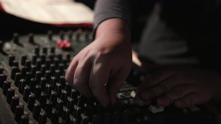 šířka pásma : work. man sits at mixing console, very focused, adjusts sound and presses keys, close-up, slow motion