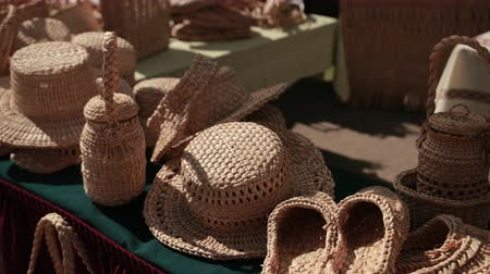 rotáng : exhibition of wicker products on street. wicker hats, baskets, handbags, Slippers are on table. handmade products fair, Sunny weather, day, close-up, slow motion Stock mozgókép