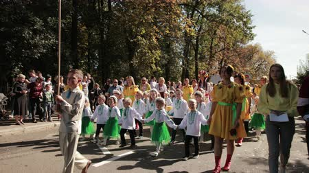 годовой : holiday on street, local parade, there are people in variety of costumes and children in embroidered shirts and national costumes, around a lot of spectators, autumn is a Sunny day, slow motion