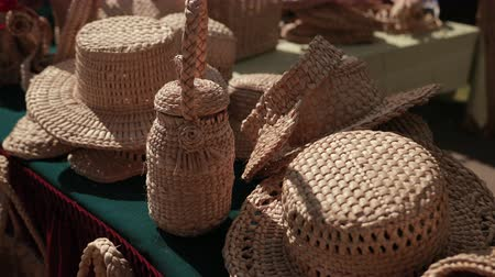 onderlegger : exhibition of wicker products on street. wicker hats, baskets, handbags, Slippers are on table. handmade products fair, Sunny weather, day, close-up, slow motion Stockvideo