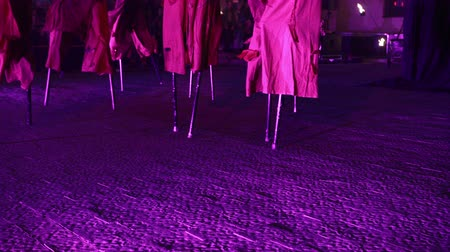 маскарад : Mysterious stilt walkers at night fire show. Closeup of stilts, theatrical costumes, moving, walking on ground with purple light.